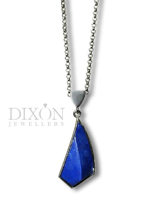 "Asymmetrical lapis lazuli set in 14kt white gold by our in house design team. Very sleek and modern! Pendant (not including bale) measures just under 1"" long."