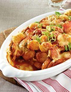 Currywurst-Gnocchi-Auflauf Rezept: Lauchzwiebeln,Bratwürstchen,Öl,Kühlregal,Curry,Tomatenketchup,Gemüsebrühe,Pfeffer,Emmentaler