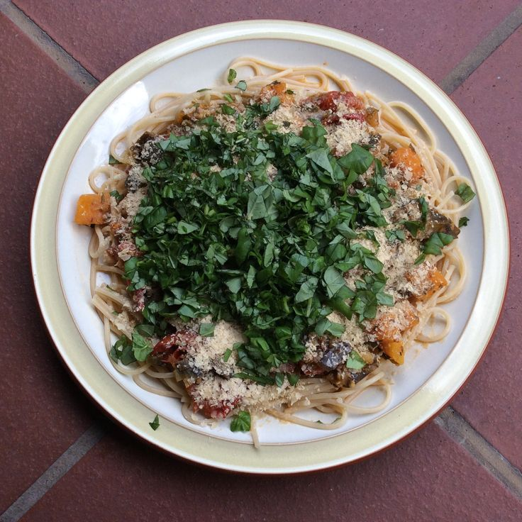 Spaghetti met een saus van lente-ui, aubergine, pompoen en tomaat, met basilicum en voedingsgist
