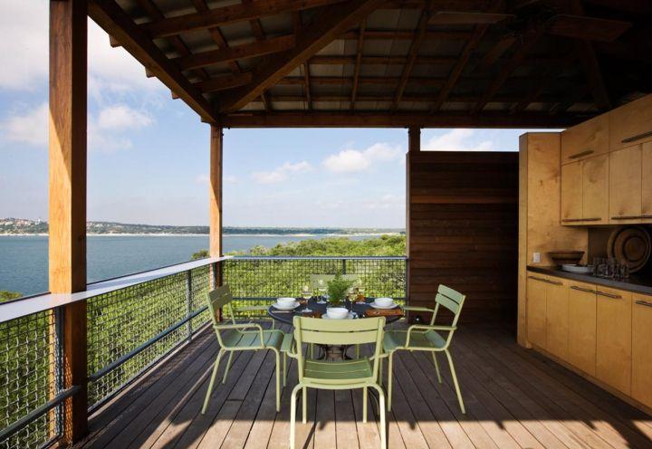 Tower House in Texas: una tettoia in legno protegge la terrazza all'ultimo piano dalla pioggia, dando vita a un vero e proprio living all'aperto, con tanto di angolo cottura disegnato su misura e realizzato in compensato di betulla