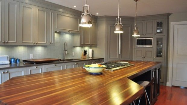 Natural wood countertop, a trendy grey finish on the cabinets and chrome hanging lights over the espresso finished island make this kitchen the hub of the house.