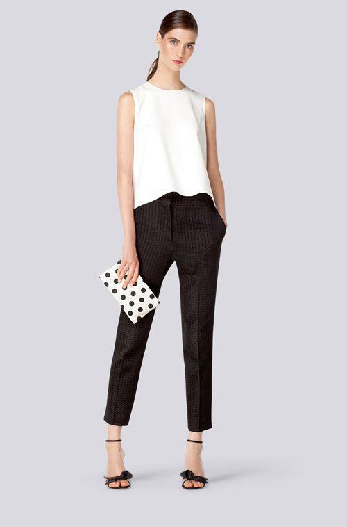 Pantalone Capri nero gessato con top sbracciato bianco, pochette a pois black and white e sandali con cinturino alla caviglia neri.