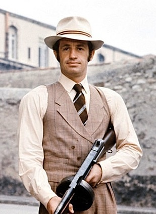 JEAN-PAUL BELMONDO: A Macho-ne gun (Thompson 45) + White Borsalino. Still from 'Borsalino' (1970)