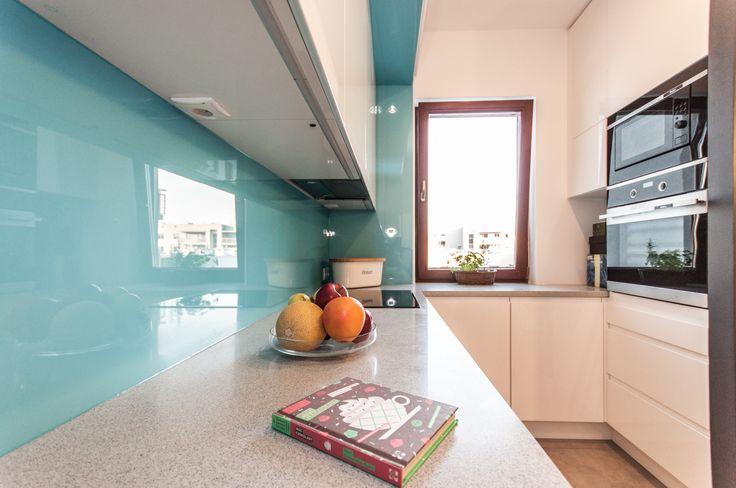 Turkusowe szkło nad blatem w kuchni.