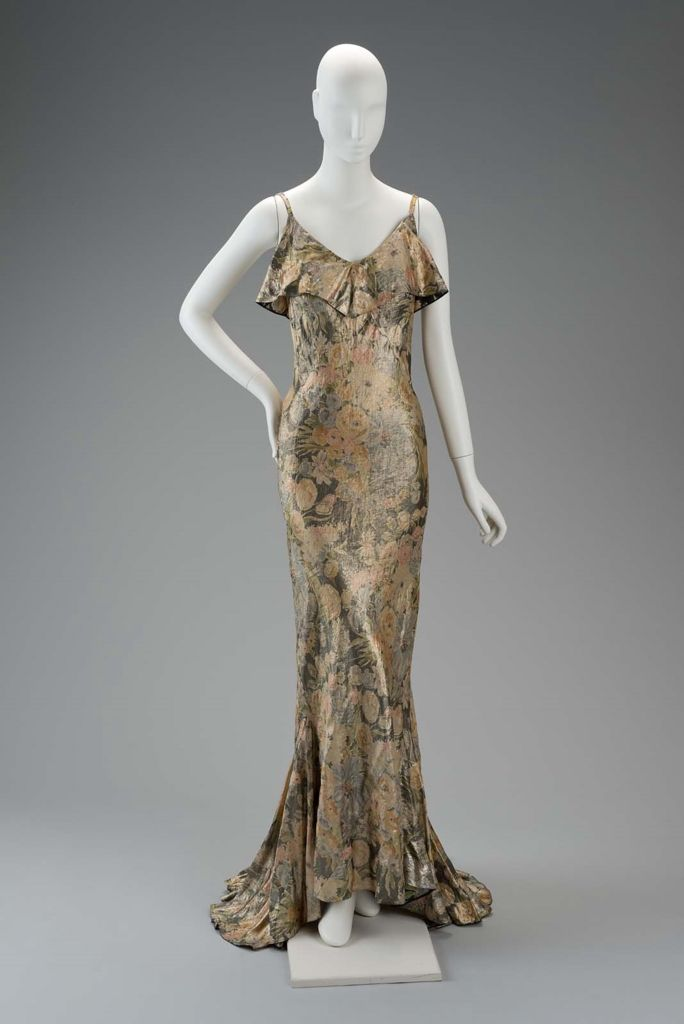 Mainbocher  1930s   Floral gold lame bias cut gown. Constructed in a combination of panels and pieces hand sewn together in a bias pattern. In lieu of a lining the lame is double faced with interior fabric identical to lame pattern but made of colorful silk charmeuse.