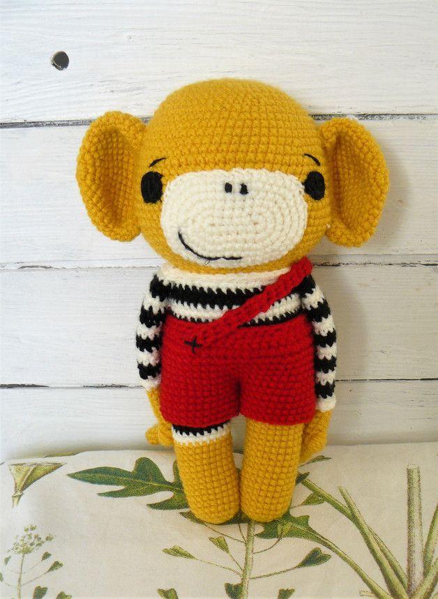 Liebevoll gehäkelter Affe **Alex**, sucht einen neuen Freund. Alex ist gelb und trägt eine schwarz/creme gestreiftes Shirt und rote Schorts. **Alex** eignet sich zum spielen, sammeln, dekorieren...