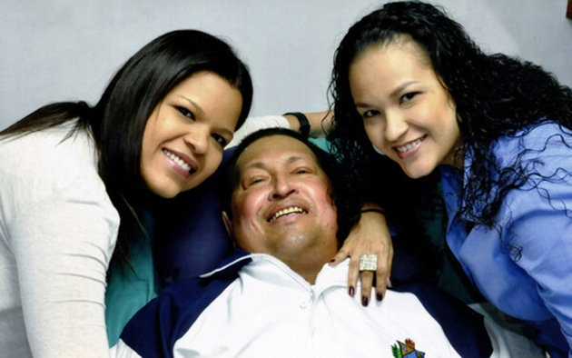 Venezuela's President Hugo Chavez smiles in between his daughters, Rosa Virginia (R) and Maria while recovering from cancer surgery in Havana in this photograph released by the Ministry of Information on February 15, 2013. Venezuela's government published the first pictures of cancer-stricken Chavez since his operation in Cuba more than two months ago, showing him smiling. Dies at age 58