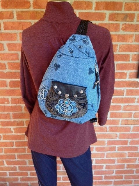Unique, casual yet classy, fun and feminine sling bag.  It's just the perfect size.   This bag was made using recycled materials.  The  front of the bag is made of denim with black floral embroidery.  The back of the bag is soft pin wale corduroy, which is a blue, black and dark tan paisley pri