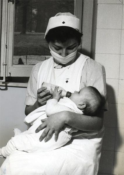 Une infirmière de la Croix-Rouge française donnant le biberon à un enfant - Outre les hôpitaux civils des dispensaires sont ouverts dans les quartiers pauvres et dans les quartiers ouvriers : le premier Porte de Vanves.