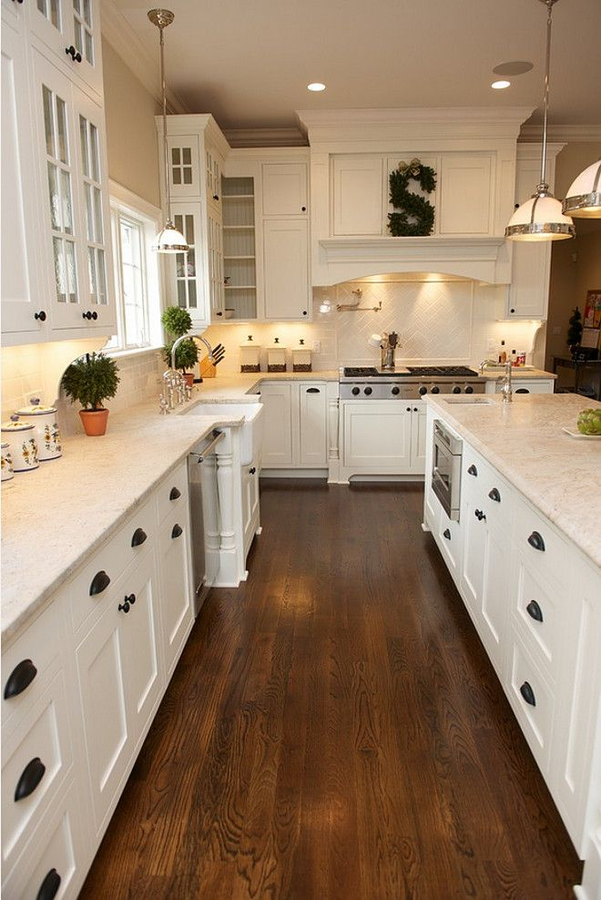 This is a traditional kitchen with contemporary features. Painted white, shaker style inset cabinetry. Dramatic wood hood. Glass door wall cabinets. #kitchen East Hill Cabinetry