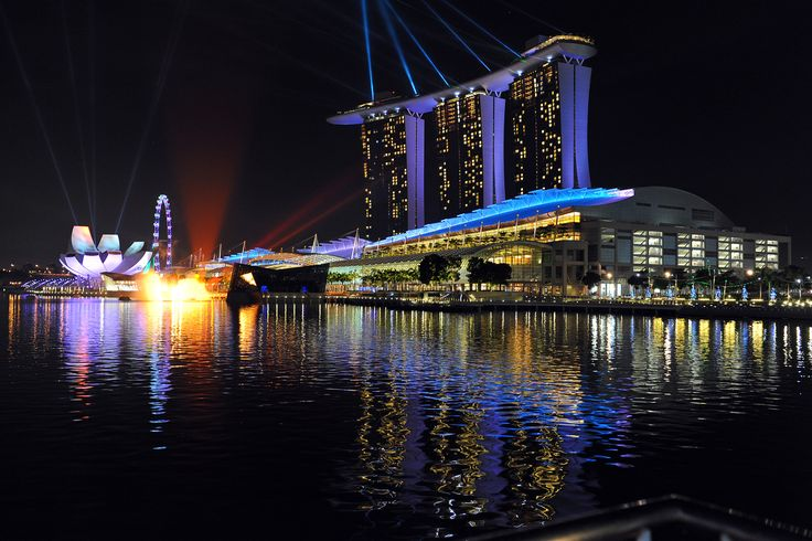 """Marina Bay Sands is an integrated resort fronting Marina Bay in Singapore. Developed by Las Vegas Sands, it is billed as the world's most expensive standalone casino property at S$8 billion, including cost of the prime land. With the casino complete, the resort features a 2,561-room hotel, a 1,300,000-square-foot (120,000 m2) convention-exhibition centre, the 800,000-square-foot (74,000 m2) The Shoppes at Marina Bay Sands mall, a museum, two large theatres, seven """"celebrity chef""""…"""