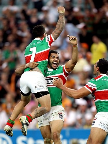Greg Inglis celebrates with teammates Adam Reynolds (L) and John Sutton after kicking the winning field goal in extra time during Wests Tigers v South Sydney Rabbitohs NRL game at Allianz Stadium in Sydney.