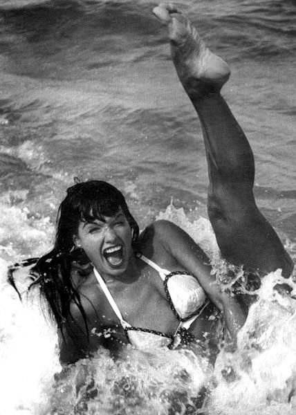 "Bettie Page - Bettie Mae Page (April 22, 1923 – December 11, 2008) was an American model who became famous in the 1950s for her pin-up photos.Often referred to as the ""Queen of Pinups"", her jet black hair, blue eyes, and trademark bangs have influenced artists for generations."