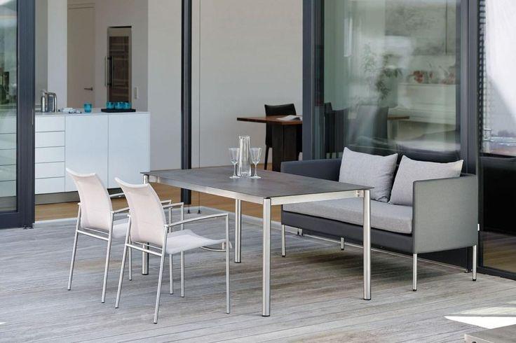 MIGUEL sofa, SKAGEN dwa wygodne krzesła i nowoczesny stół.  MIGUEL sofa dwuosobowal, która spełnia dwie funkcje: DINING i LOUNGE. Sofa do użytku zewnętrznego ze specjalnej tkaniny w kolorze antracytowym i szybko przesiąkliwej gąbki na aluminiowej ramie w optyce stali szlachetnej. Poduszki (100% Polyester) w kolorze szary melanż są bardzo miłe w dotyku.  SKAGEN nowoczesne krzesło ze stali nierdzewnej i tkaniny Stricktex (100% Polyester) w jasnoszarym kolorze. Krzesła do wykorzystania we…