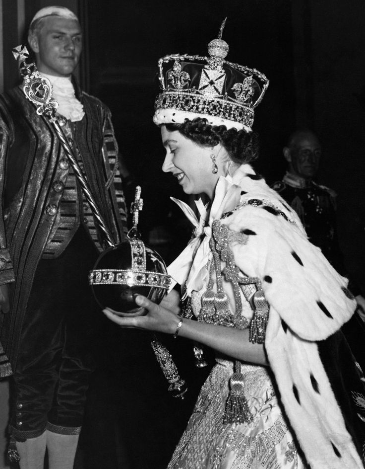 Queen Elizabeth wearing the Impertial State Crown and carrying the Orb, as she arrives at Buckingham Palace after the Coronation ceremony at Westminster Abbey.