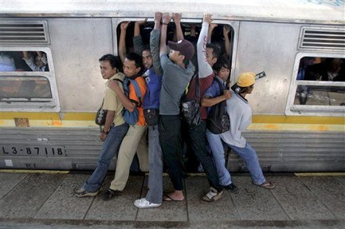 Go to work.Indonesian men struggle to board a packed commuter train at a station in Jakarta