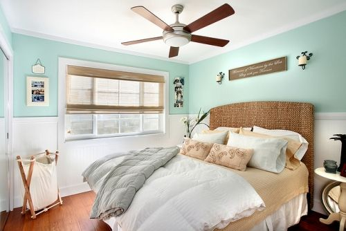 Aqua green, wicker headboard, sandy tan sheets, wood sign, screen blind, white wainscoting.