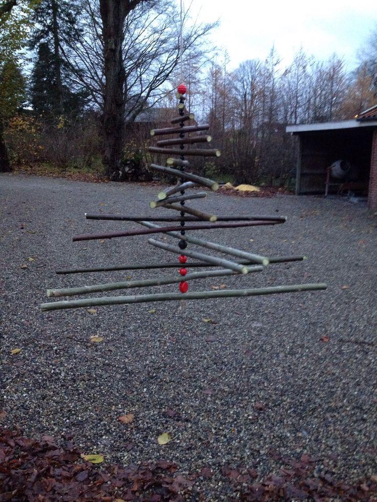 Supernemt at lave. Pil fra haven og genbrugsperler.  Lav en trekant på et stykke pap. Læg grenene på og klip. Bor hul midt i alle pinde og træk på snor