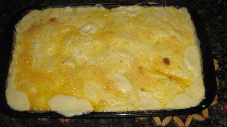 1/2 kg de filé de peixe (pargo, piramutaba ou dourado)  - Suco de 1 limão  - Sal e pimenta do reino branca moída na hora a gosto  - Farinha de trigo (para empanar o peixe e engrossar o creme)  - 1 xícara de chá de caldo de peixe ou de legumes  - 2 xícaras de leite fervente  - 3 colheres de sopa de manteiga  - 1 cebola média ralada em ralo grosso  - 1 lata de creme de leite  - 200 g de queijo mussarela fatiados  - 5 bananas cortadas na diagonal e fritas na manteiga  - 3 colheres de sopa d...