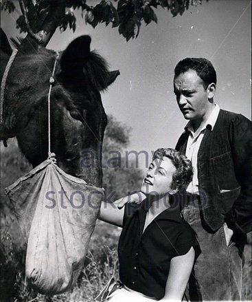 0 french actress gisele pascal feeding a horse next to raymond  pellegrin