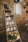 Step ladder table plan with candles, glass jars filled with flowers and strung up stationery