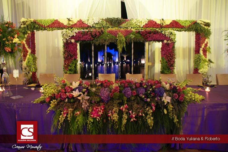 Boda Yuliana & Roberto mesa en forma de herradura con arcos con flores en la parte trasera