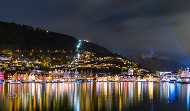 "Night in Bergen - A night in Bergen harbor, you can see the old wharf ""Bryggen"" to the left, the funicular ""Fløybanen"" near the middle going up the mountain and to the right in the back the mountain ""Ulriken""."