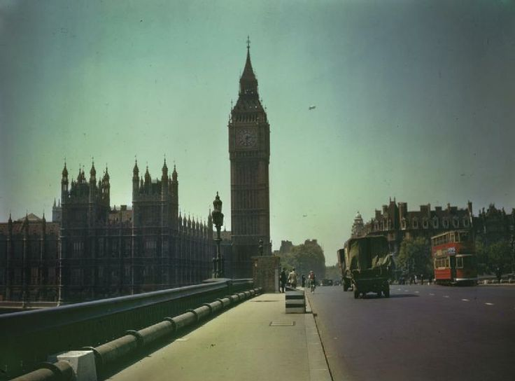 Big Ben and the Houses of Parliament in London with barrage balloons in the background, seen from Westminster Bridge (on which a sentry, military vehicles and a tram can be seen). c.1944.