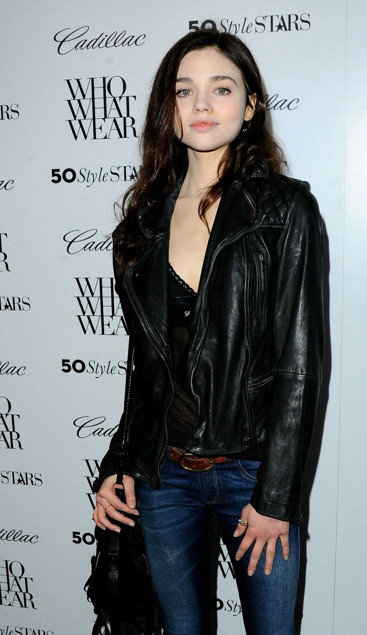 India Eisley; simple makeup, leather jacket, denim with a brown belt and black feathered bag.