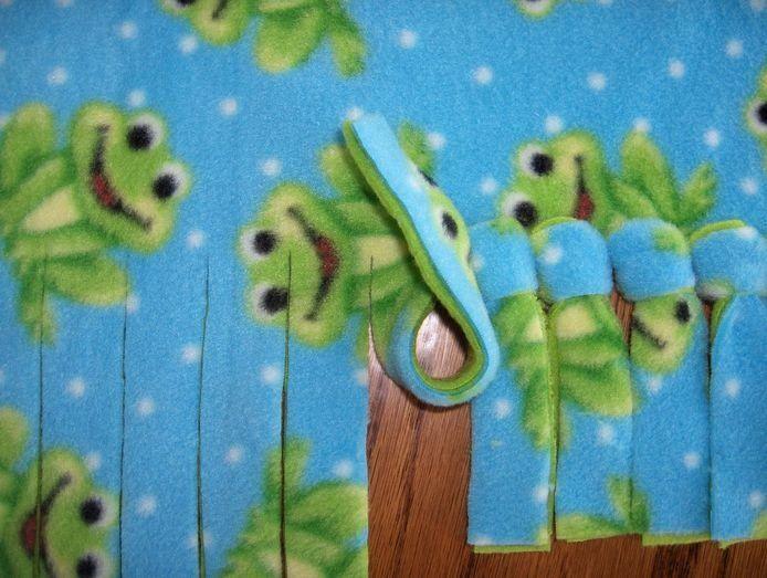 Для создания этого уютного одеяла совсем не нужны нитки - только ножницы и 2 тонких флисовых пледа.