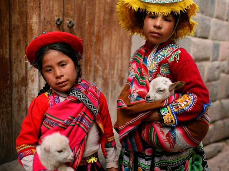 Dressed in traditional clothing, two children hold lambs and pose for a portrait in Peru.