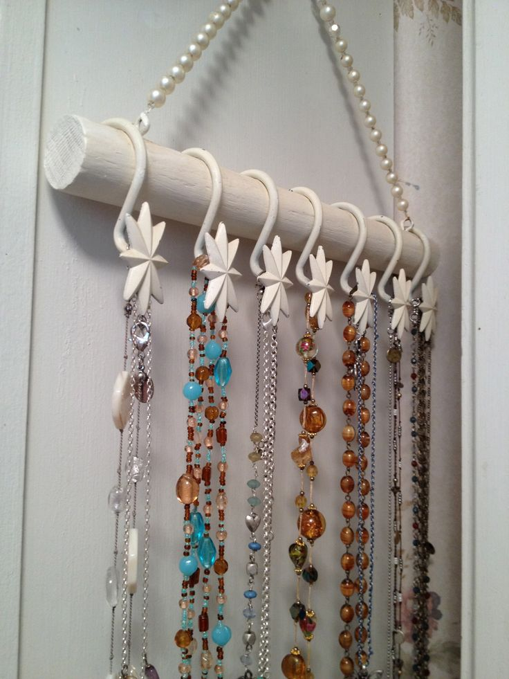DIY jewelry hanger made with shower curtain hooks, a painted wooden dowel and a vintage necklace for hanging