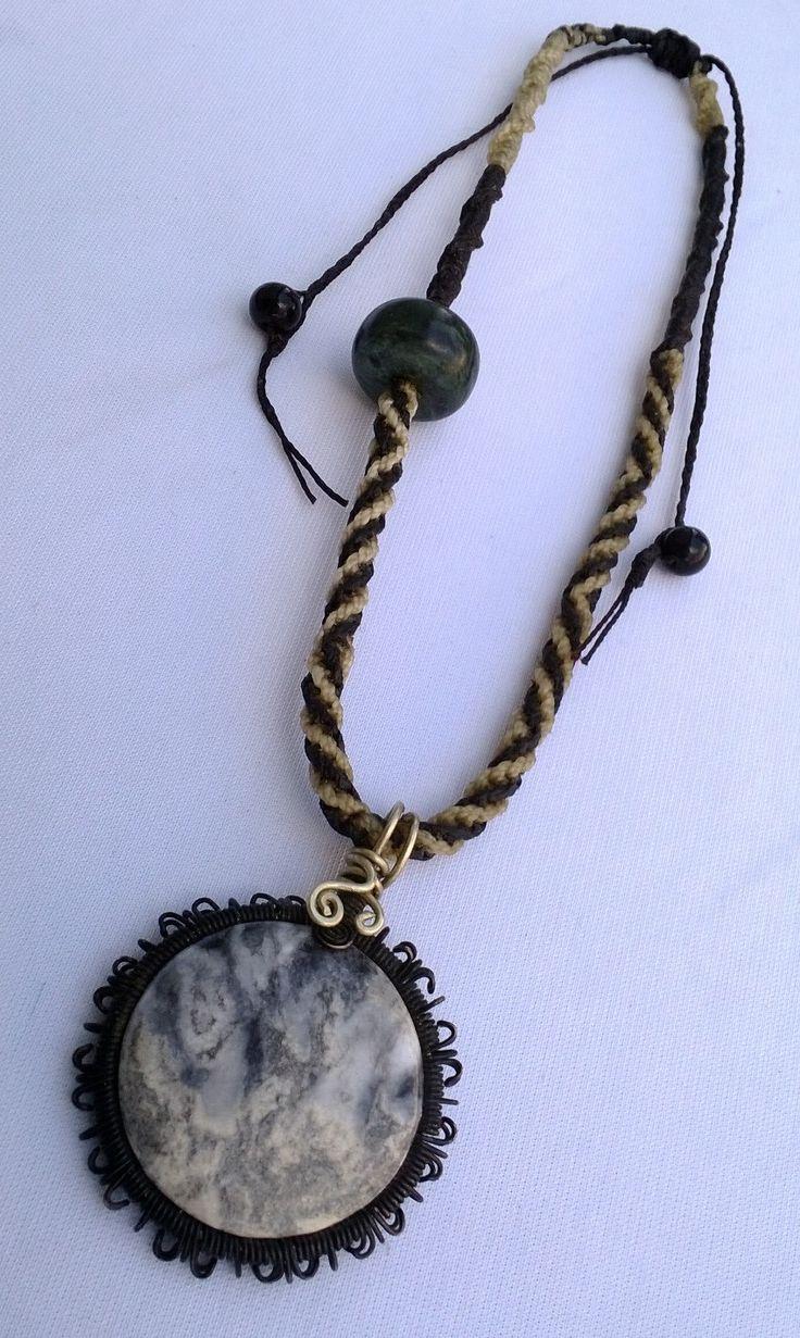 Piedra natural engarzada con alambre pavonado, cordón tejido a mano y una pieza de jade.