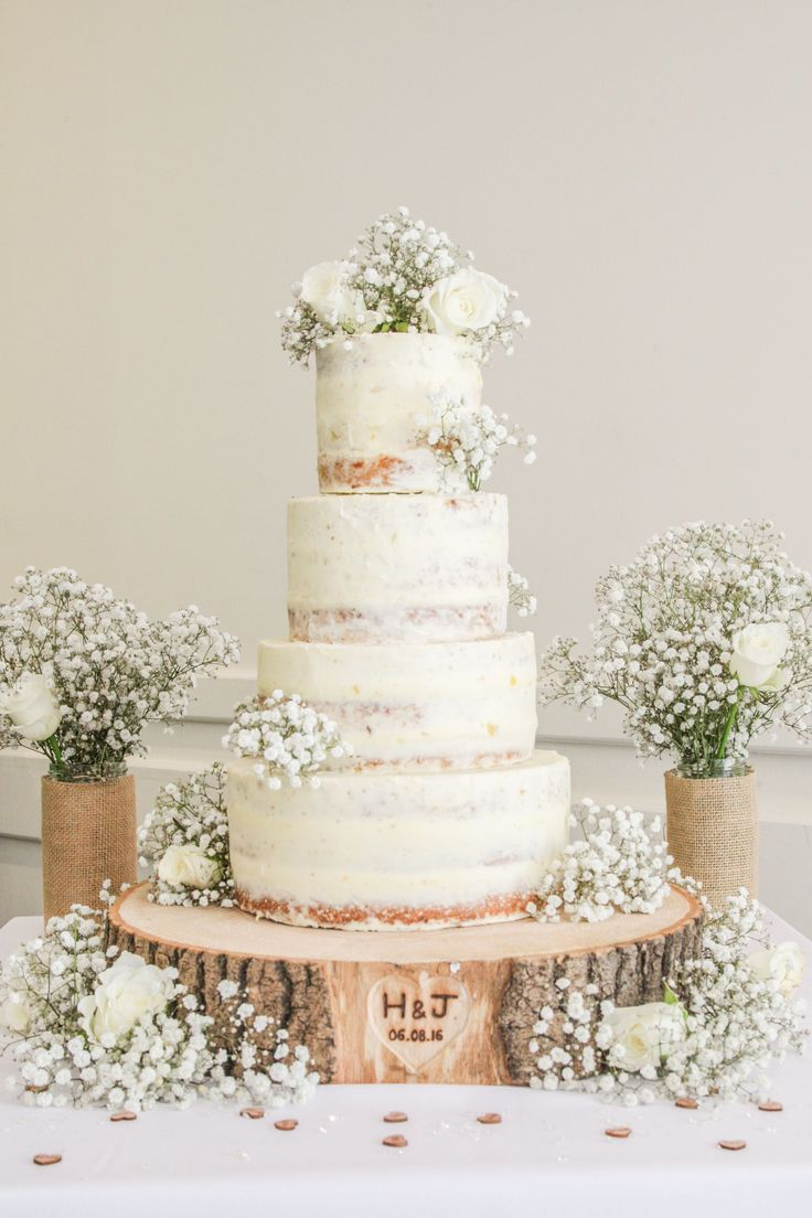 Semi naked limoncello 4 tier wedding cake on a engraved log slice. Surrounded by homemade burlap vases filled with white roses and babies breath. Elegantly rustic.