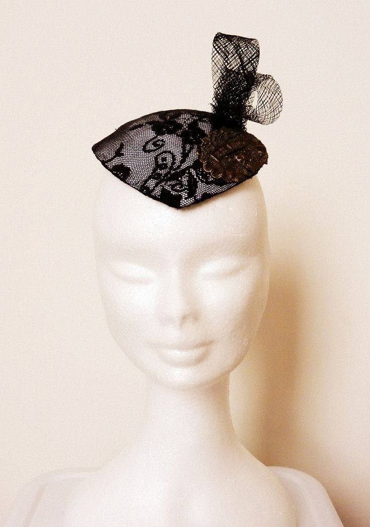 """Race hat? Melbourne Cup hat White silk base covered with vintage black lace. Black sinamay triple looping feature, bronze voloured metal """"Brandy"""" vintage style liquor tag."""