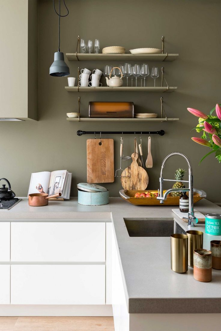 I love this grey-tinted green shade in this kitchen; it looks great with the concrete surface and white cabinets; the paint colour lifts the space from ordinary to unusual.