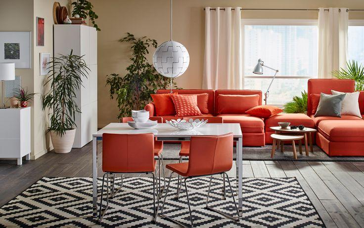 クロムメッキの脚とホワイトのハイグロステーブルトップの4人用のダイニングテーブル。オレンジの革にクロムメッキの脚のチェアが4脚。