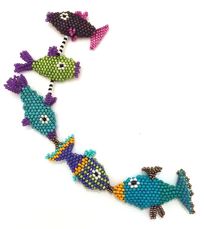 Nita E Kaufman - working on a fishey necklace.