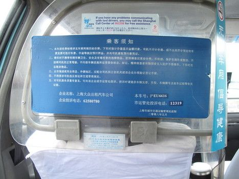 Inside a taxi cab, all Chinese except for instructions to call the Shanghai Call Center when encountering communication problems with the taxi driver
