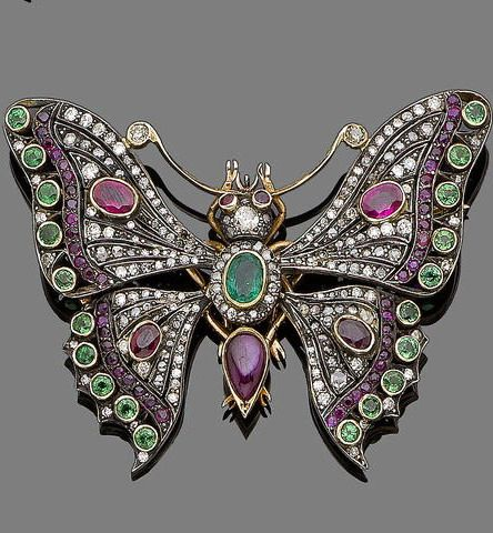 A diamond, ruby, emerald and tsavorite butterfly brooch The body set with an oval-cut emerald and rose-cut diamond cluster and a cabochon ruby, the pierced wings set with old brilliant, single and rose-cut diamonds and decorated with oval and circular-cut rubies and collet-set circular-cut tsavorite garnets, diamonds approx. 0.70ct total, one diamond deficient, length 7.4cm