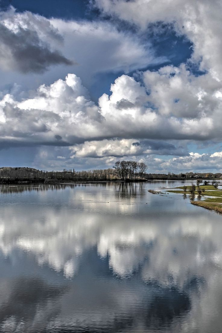 Reflection of a dramatic sky in the rising waters of the IJssel river in the floodplains near Deventer