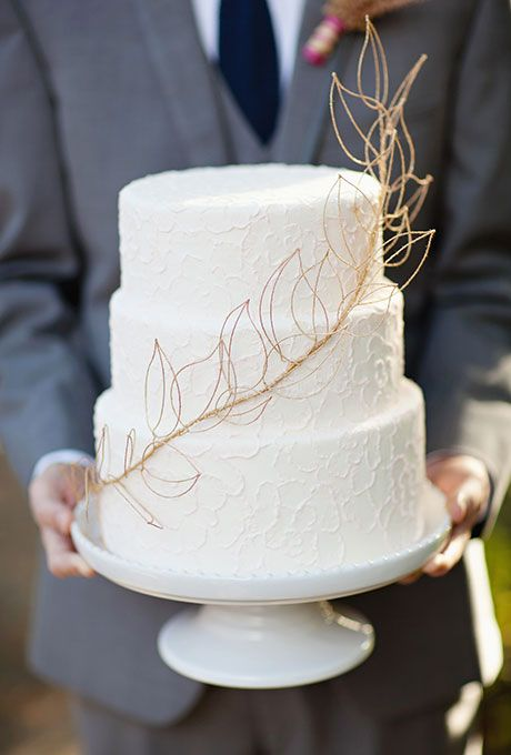 A three-tiered white wedding cake with metallic gold leaf details by Anne Kathleen Cakes