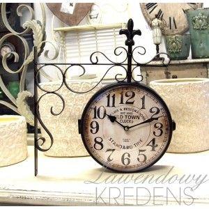 Metalowy zegar kolejowy ozdobiony metalową lilijką.