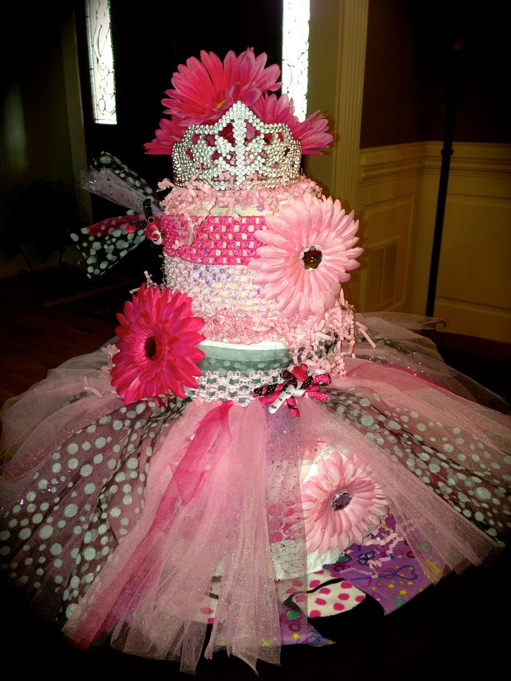 I made this Diaper Cake today for a shower to honor a fellow ballet teacher that is having a new little princess in August! I used Pampers Swaddlers size 2, and made 3 tiers. 14 inch cake round as a base covered with a ballet bandana. I embellished a tutu kit from Hobby Lobby, added ballet booties etc...