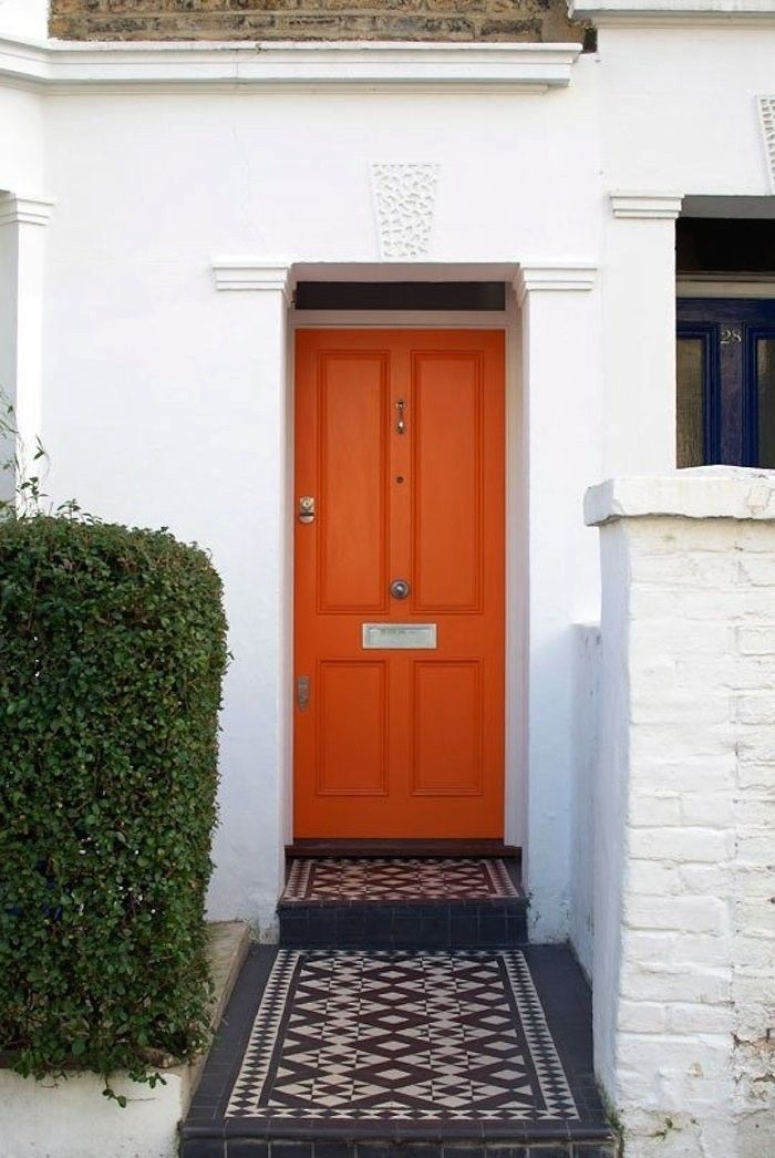 Great curb appeal. Orange front door with black and white mosaic tile front walk in London. via Gardenista