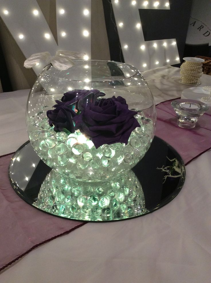 Fish bowl wedding centrepiece for purple themed weddings. Clear illuminated beads, cadburys purple roses and Ivory butterfly. Available to hire for your wedding in Swansea, Neath, port talbot, Bridgend, porthcawl, Llanelli, Carmarthen and surrounding areas of South Wales from affinity event decorators www.affinityeventdecorators.com
