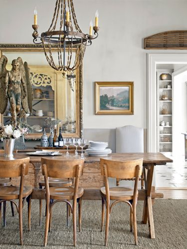An 18th-century wooden angel looks over a gorgeous antique pine trestle table in this dining room. #decoratingideas