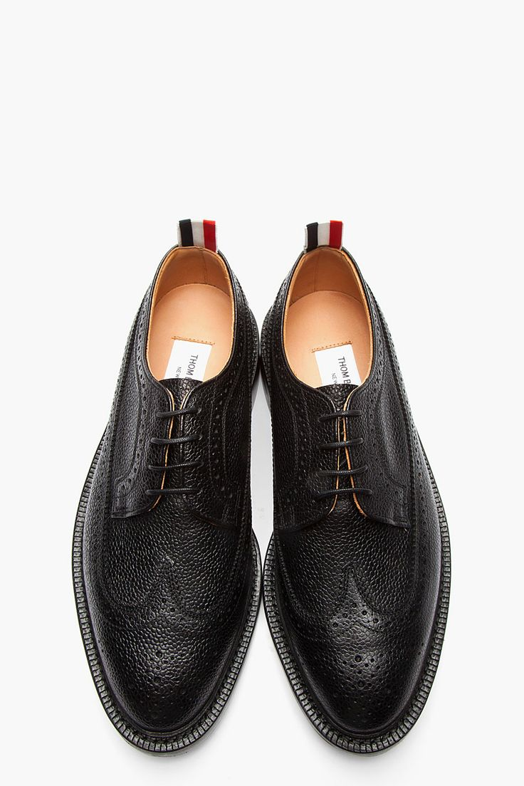 THOM BROWNE //  Black Scotchgrain Leather Longwing Brogues  32381M049001  Low top scotchgrain leather longwing brogues in black. Round toe. Tonal lace up closure. Signature perforated detail and serrated edges throughout. Signature tricolor pull loop at heel collar. Tonal welt and foxing. Tonal stitching. Leather upper, leather sole. Made in United Kingdom.  $860 CAD