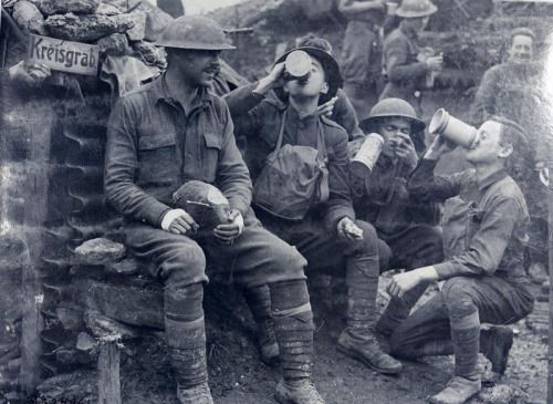 American soldiers of the 33rd Infantry Division enjoying beer, bread, and cigars abandoned by the Germans in a trench near Consenvoye, 1918.