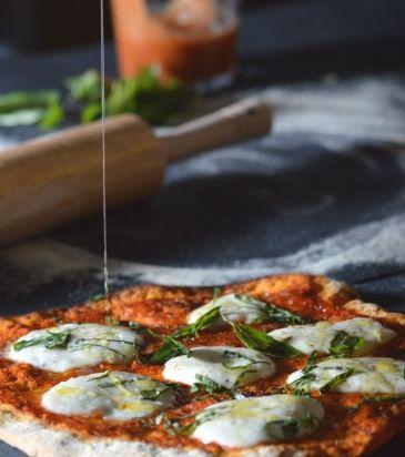 Ανοίγουμε τη ζύμη στρογγυλή και την ακουμπάμε στο αντικολλητικό τετράγωνο ταψί του φούρνου, απλώνουμε τη σάλτσα ντομάτα ομοιόμορφα.